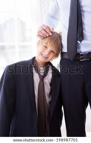 I want to be like my father. Cheerful little boy playing with necktie of his father standing near him and smiling at camera - stock photo