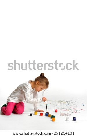 I want to become a great artist! Little girl is drawing on white floor.  - stock photo