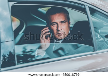 I will be in time. Confident mature businessman talking on the mobile phone and looking away while sitting on the back seat of a car - stock photo