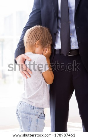 I will be missing you! Little boy crying and covering face with hands while his father in formalwear consoling him  - stock photo