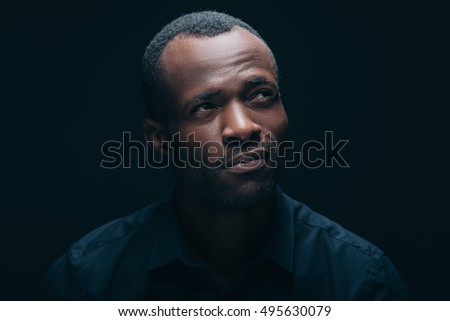 I will think about it. Portrait of handsome young African man looking thoughtful while being in front of black background