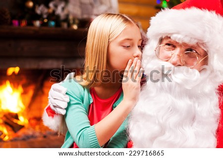 I wish? Happy little girl sitting on Santa Claus knees and whispering something at his ear with fireplace in the background - stock photo