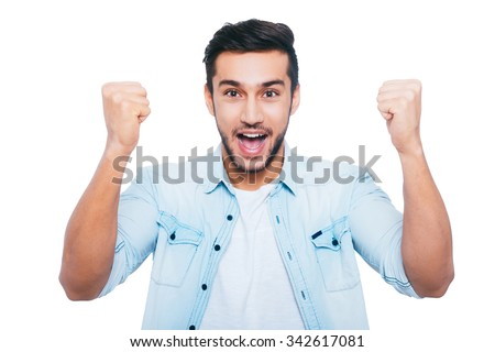 I won! Happy young Indian man gesturing and smiling while standing against white background