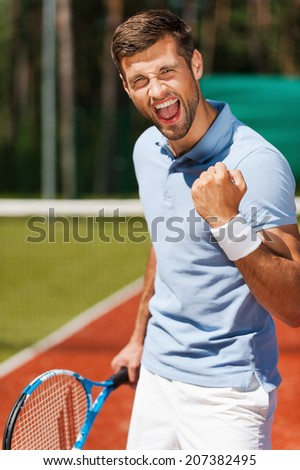 I won! Happy young man in polo shirt holding tennis racket and gesturing while standing on tennis court  - stock photo