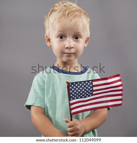 I young boy holds tightly on to the American flag. - stock photo