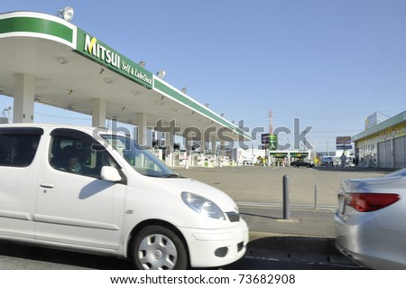 IBARAKI PREFECTURE, JAPAN - CIRCA MAR 2011: Hundreds of cars wait in line for the closed gas station to reopen in Ibaraki Prefecture circa March 2011. After the earthquake, there is a shortage of fuel - stock photo