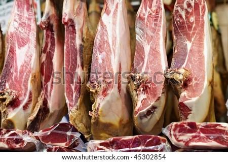 Iberian ham (spanish prosciutto or jamon iberico) hanging at local butcher in Barcelona, Spain - stock photo