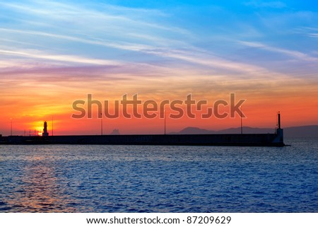 Ibiza mountains on red sunset view from Formentera marina - stock photo