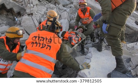 IBTIN, ISRAEL - DECEMBER 17, 2015: Israeli Homeland Security Soldier carry injured soldier on stretcher during earthquake rocket attack tsunami drill after digging through the rubble - stock photo