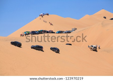ICA, PERU - JAN. 06: A espectator off roader group climb a big dune to watch the race, on Rally Dakar 2013, JAN 06, 2013 in Ica, Peru. - stock photo