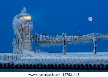 Ice accumulates on the St. Joseph North Pier Lighthouse at dusk in the Winter in Saint Joseph, Michigan on February 6, 2013 - stock photo