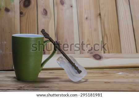 ice and a green cup on a wood