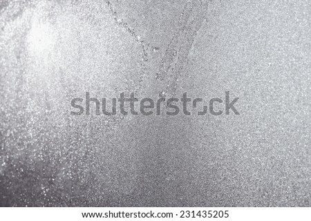 Ice and frost background over the sun on frozen window. Colored in silver or grey tone. Selective focus at center with blur edges of image - stock photo