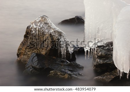 Ice and icicles on coastal rocks at the lake.