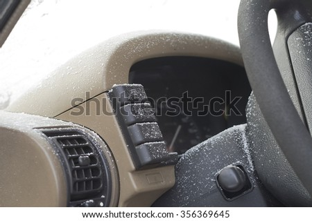 Ice and snow on a car dashboard and power steering, selective focus shot - stock photo