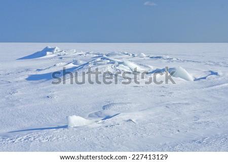 Ice and snow on a sunny sea, ocean. Continuous, unbroken winter white sea in bright sunshine. - stock photo