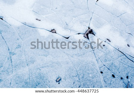 ice background texture with a long crack and rock - stock photo