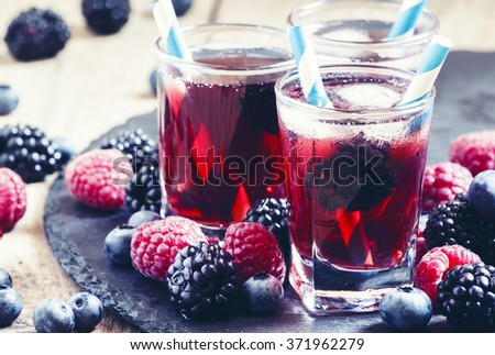 Ice berry tea with raspberries, blackberries and blueberries, selective focus - stock photo