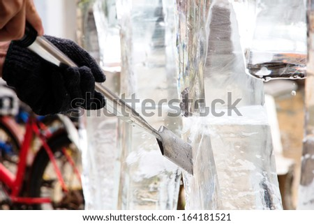 Ice Carver Using Chisel to Carve  - stock photo
