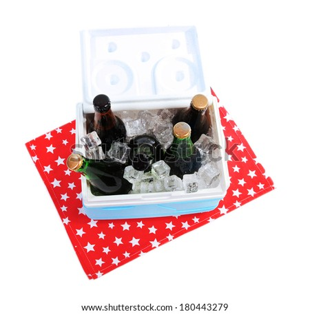 Ice chest full of drinks in bottles on color napkin, isolated on white - stock photo