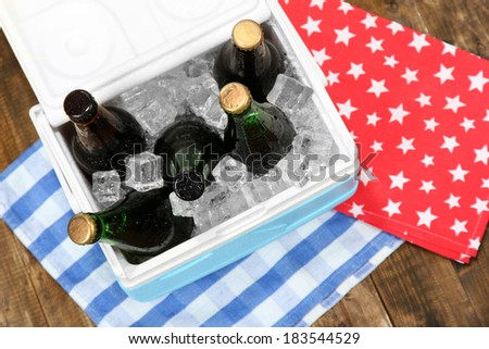 Ice chest full of drinks in bottles on color napkin, on wooden background - stock photo