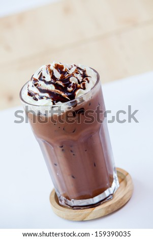 Ice chocolate with whipped cream on table