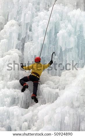 Ice climber on steep frozen waterfall - stock photo