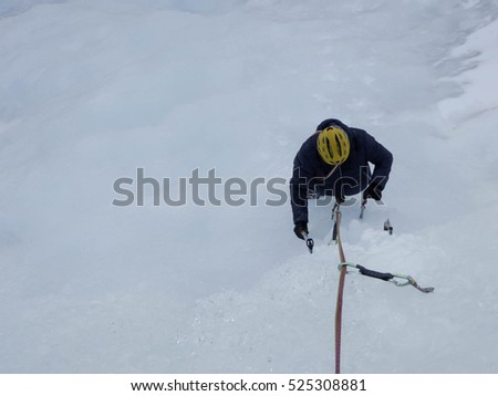 ice climber removing an ice screw on an ice fall in the Swiss Alps