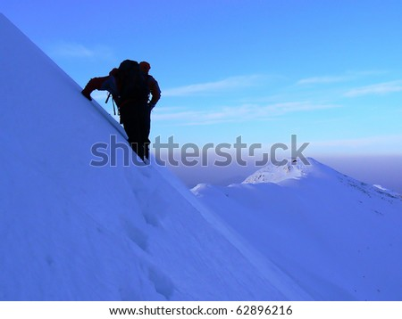 Ice climbing in Piatra Craiului mountains in winter.Piatra Craiului it's a mountain range in the southern Carpathians in Romania.The Piatra Craiului mountains form a narrow and saw-like ridge. - stock photo