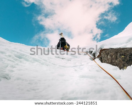 Ice climbing: mountaineer on a mixed route of snow and rock during the winter. Western Alps, Italy, Europe. - stock photo