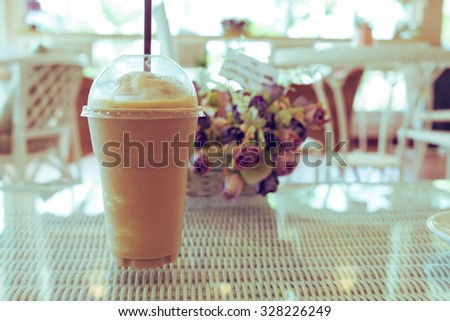 ice coffee frappe on table, plastic cup of coffee in cafe - stock photo