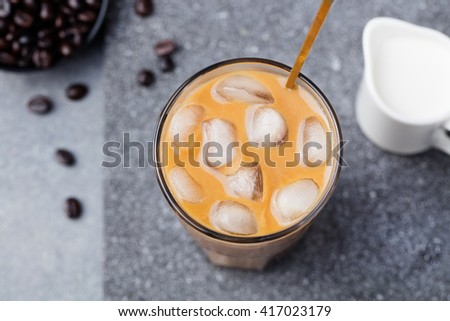 Ice coffee in a tall glass with cream and coffee beans on a grey stone background Top view Copy space - stock photo