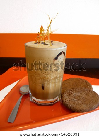 Ice coffee milkshake above an orange plate with two delicious chocolate cookies - stock photo