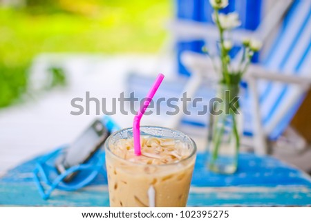 ice coffee on grunge wood table in garden - stock photo