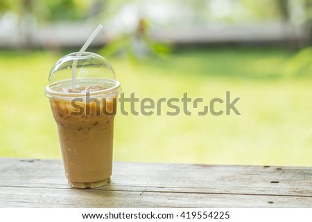 ice coffee on wood table with blur green background  with copyspace - stock photo