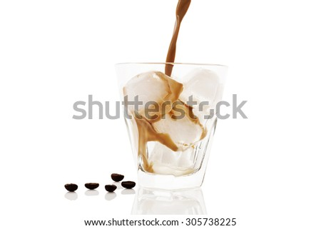 Ice coffee. Pouring ice coffee into glass with ice isolated on white background. Delicious coffee drinking.  - stock photo