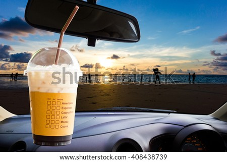 Ice coffee, sunset on the beach at the windshield as background. - stock photo