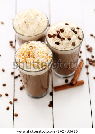 Ice coffee with whipped cream and coffee beans on a white table - stock photo