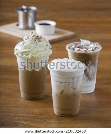 Ice coffee with whipped cream and coffee beans on wooden table. - stock photo