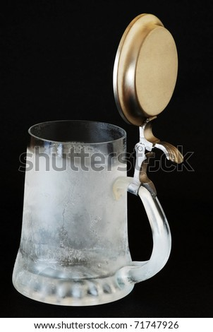 Ice cold beer mug with pewter lid ready to be filled with beverage on dark background. - stock photo