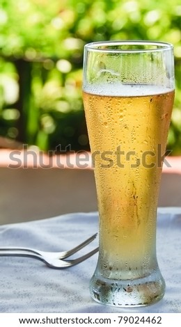 Ice cold beer. Tall frosty glass of cold beer in outdoor jungle restaurant promises relief from thirst and heat. - stock photo