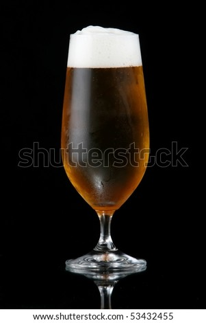 Ice cold beer with frothy head against black background - stock photo
