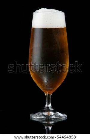 Ice cold beer with frothy head against black background