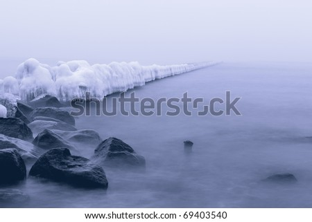 Ice-covered coastal protection during the winter fog. shot at long exposures. - stock photo