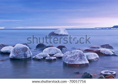 ice-covered rocks on the shore of the Baltic Sea, photographed on a winter evening at long exposures - stock photo