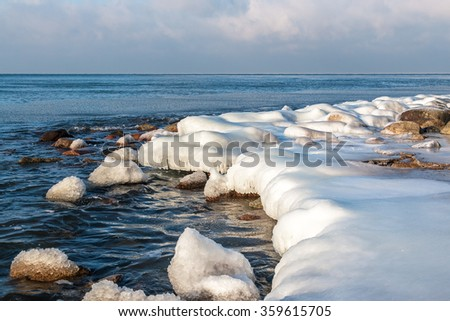 Ice covered stones of the Baltic seashore at sunny winter day