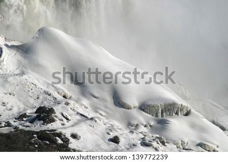 Ice covered stones under Niagara waterfall - stock photo