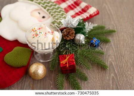 Ice cream and Santa Claus. Cold dessert for the new year. Gift sock in the form of Santa Claus and ice cream in a vase. New Year's composition. White ice cream and Santa Claus.