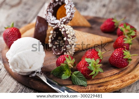 ice cream and strawberries on a wooden table - stock photo