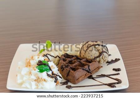 ice cream , banana , chocolate waffles with chocolate sauce and whipping cream - stock photo